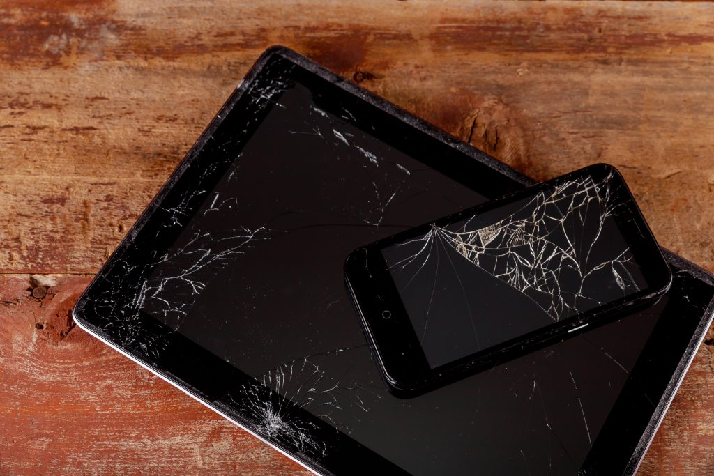 Broken electronic device on wooden background touch screen